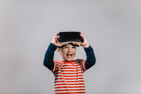 Portrait of cheerful child wearing virtual reality headset against grey background. Smiling happy boy enjoying virtual reality with VR glasses.