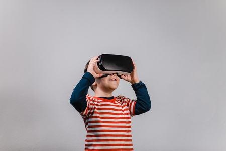 Excited kid having fun with VR glasses. Portrait of cheerful child wearing virtual reality headset against grey background. Фото со стока