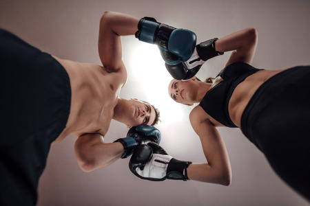 Male and female kick boxers standing against each other with boxing gloves in ring. Low angle view of man and woman at kick boxing fighting position.