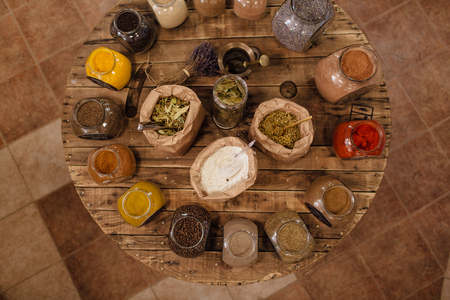 Variety of colorful dried herbs and spices displayed on round wooden table in plastic free store. Top view of bags and glass jars full of whole and ground spices and herb leaves in packaging free shop. Фото со стока