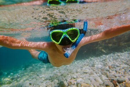 Child snorkeling in shallow sea. Young boy wearing diving mask and snorkel looking into camera underwater.