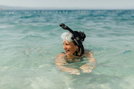 Cheerful woman wearing diving mask and snorkel swimming in water. Snorkeling - happy female diver enjoying being in sea. 스톡 콘텐츠