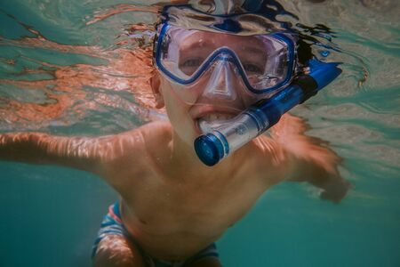 Happy child snorkelling. Young boy wearing diving mask and snorkel swimming in sea.