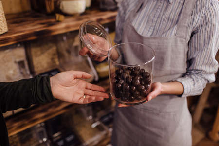Shop assistant holding glass jar with healthy chocolate balls in organic store. Zero waste shopping - hand of customer pointing at fresh sweets in package free food store. Stock Photo