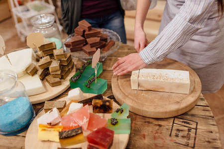 Shop assistant cutting bars of natural soap for customer in package free store. Display of colorful handmade organic soaps in packaging free shop. Stock Photo