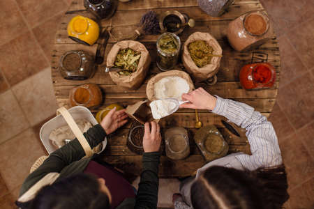 High angle view of shop assistant putting flour into paper bag for customer at zero waste shop. Top view of women standing at round table with herbs and spices in package free store.