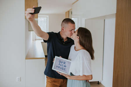 First time buyers kissing and holding digital tablet with 'our new house' taking photo of themselves on smartphone. Young couple kissing and taking selfie in new house.