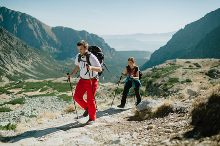 Man and woman nordic walking in the High Tatras mountains on a bright day.