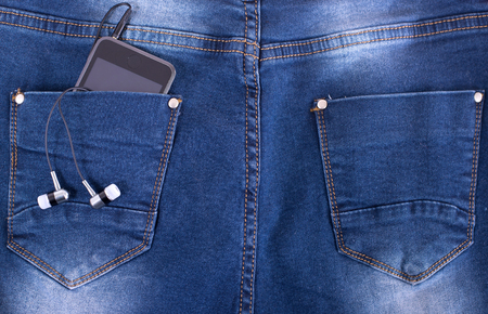 MP3 player and earphones sticking out of jeans pocket photo