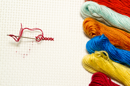 Closeup of cross-stitch: needle with thread on a white canvas with multicolored skeins of thread for embroidery on the side