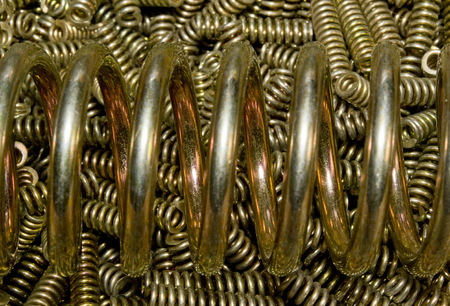 Closeup bright shiny coiled spring yellow zinc coated on the background of a pile of small golden galvanized coil springs Stock Photo