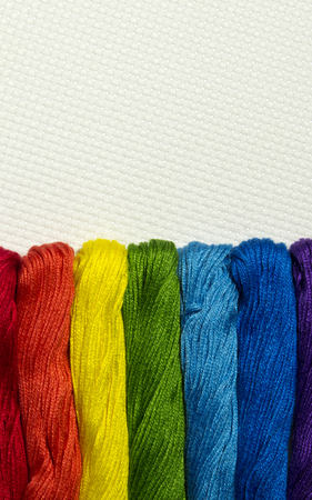 Colorful set of skeins threads for cross stitch. Bright picture with a hanks  all colors of the rainbow. Useful as background or template for design with blank space for text or inscription.