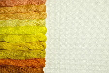 A set of threads in shades of yellow and orange for cross stitch on the side of a white canvas. Beautiful background used as template for design with blank space for text about embroidery hobby. Фото со стока