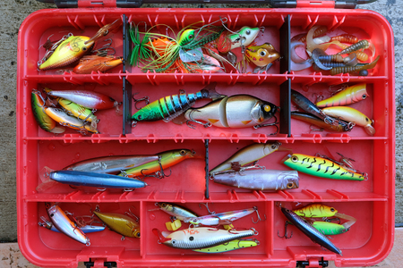 Fishing lures in the red box tool for sport holiday, weekend, and vacation project relaxation time. Stock Photo
