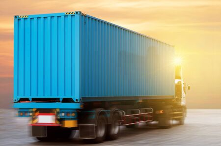Trucking is carrying blue 40' high cube container transportation with beautiful sunset sky shine on the road.