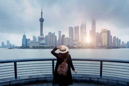 Woman tourist is enjoy watching landmark view city skyline business district in Shanghai, China. Stock Photo