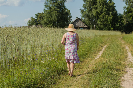 Walking woman in a straw hat among a field of rye in Belorussian village photo
