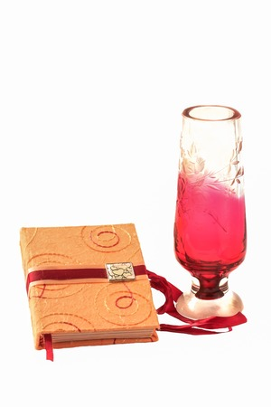 romantic memo book and colored crystal vase isolated on white background photo
