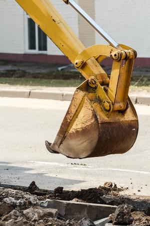 wheel loader excavator digging deep trench on sandy rocky land photo