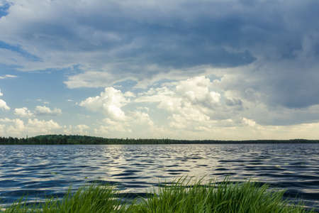 stormy waters: Dark landscape with forest lake before stormy rain