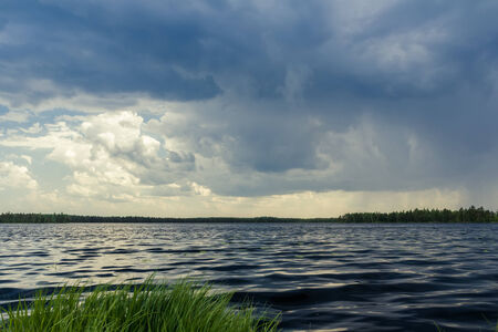 stormy waters: Landscape with dark forest lake before stormy rain