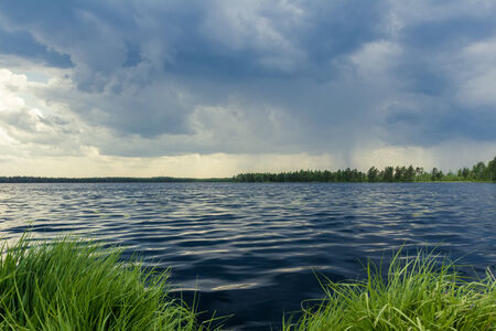 stormy waters: Dark sky on forest lake before storm rain