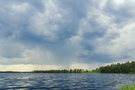 Dark storm sky on forest lake before rain photo