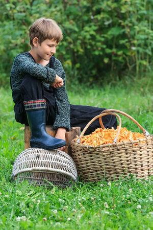 Ten years boy looking at wicker basket full of chanterelles photo