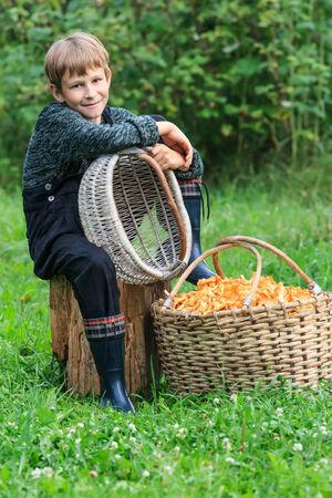 Boy sitting near basket full of chanterelle mushrooms photo