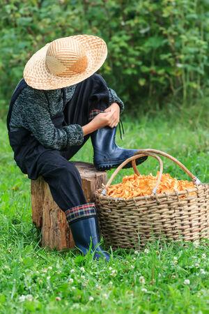 girolle: Boy wearing straw hat sits near basket full of chanterelles Stock Photo