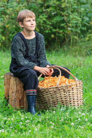 Ten years boy sitting with basket full of chanterelles photo