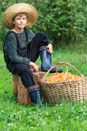 Boy wearing straw hat sits with basket full of chanterelles photo