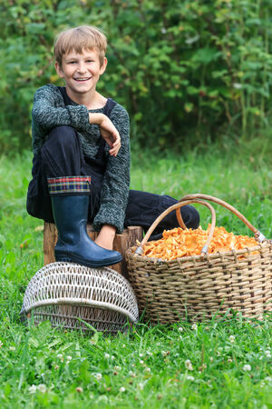 Happy teb years boy sitting near basket full of chanterelles photo