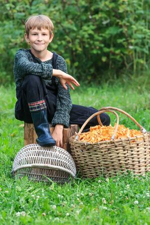 Lad sitting near willow basket full of chanterelles photo