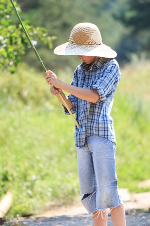 10 11 years: Portrait of teenage fisherman with stick at straw hat