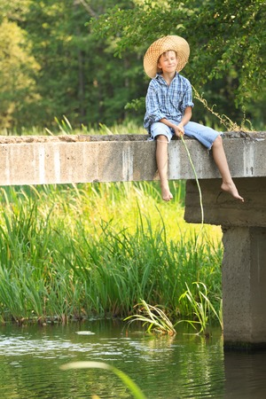 10 11 years: Boy during fishing with rod on bridge at a straw hat