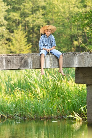10 11 years: Teenage boy fishing with rod on bridge at a straw hat