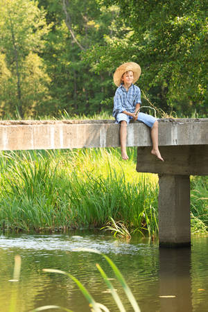 10 11 years: Boy during angling with rod on bridge at a straw hat