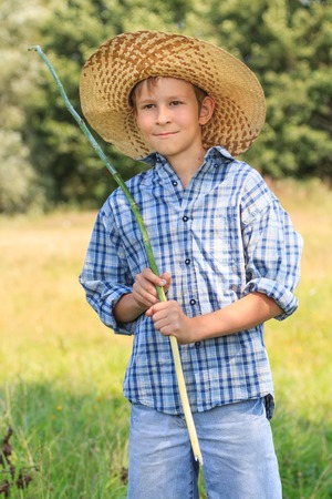 10 11 years: Portrait of teenage fisherman with rod at straw hat Stock Photo