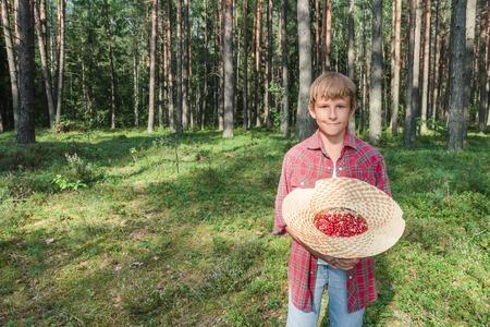 cull: Portrait of teenage boy holding straw hat full of red wildberries