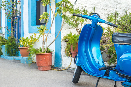 old motorcycle: Blue retro scooter at traditional Greek house background on Kalymnos island Stock Photo