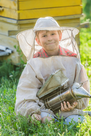 Young beekeeper boy with painted wooden beehives photo