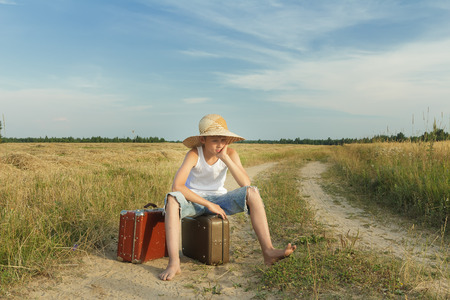 despaired: Teenage traveler waiting and sitting on a luggage