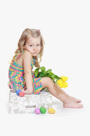 apathetic: Bored little blonde girl with Easter decorations