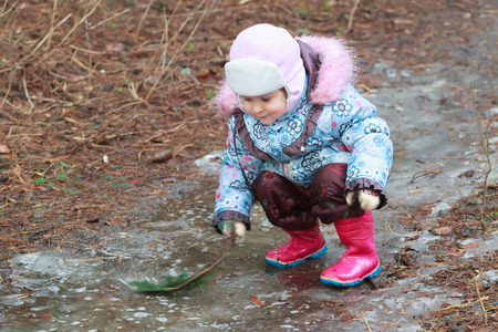 warm clothing: Little girl in warm clothing is exploring icy puddle