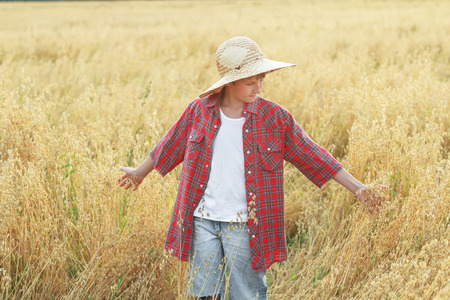 oat field: Portrait of teenage farm boy in red checkered shirt and yellow wide-brimmed natural straw hat is checking oat field