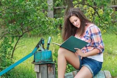 Portrait of reading long-haired brunette student girl in green summer garden photo