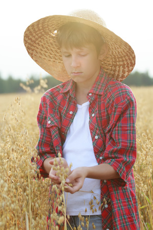 sun flare: Portrait of teenage farmer boy is holding ripe oat seeds with outer shells in cupped palms with sun flare Stock Photo