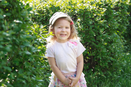 shrubbery: Two year-old laughing girl in corduroy flat cap and skirt at green garden shrubbery background Stock Photo
