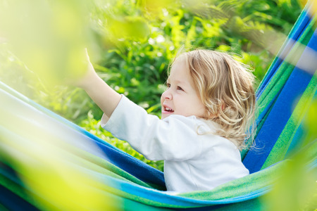 brown  eyed: Two year-old toddler girl is laughing and playing in striped blue-green Brazilian hammock in summer garden